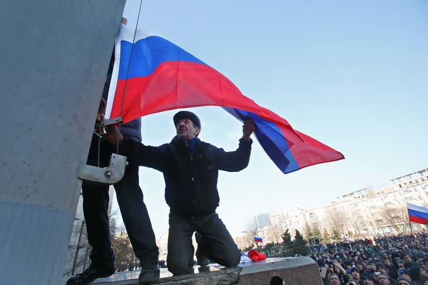 "People prepare to hoist a Russian flag on the spire in front of the regional administrative building during a pro Russian rally in Donetsk, eastern Ukraine, Sunday, March 9, 2014. Following an extraordinary meeting of the Ukrainian government, Prime Minister Arseniy Yatsenyuk announced he would be flying later this week to the United States for high-level talks on ""resolution of the situation in Ukraine,"" the Interfax news agency reported Sunday. (AP Photo/Sergei Grits)"