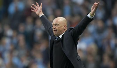Wigan's manager Uwe Rosler celebrates as his team beat Manchester City 2-1 during their English FA Cup quarterfinal soccer match at the Etihad Stadium, Manchester, England, Sunday, March 9, 2014. (AP Photo/Jon Super)