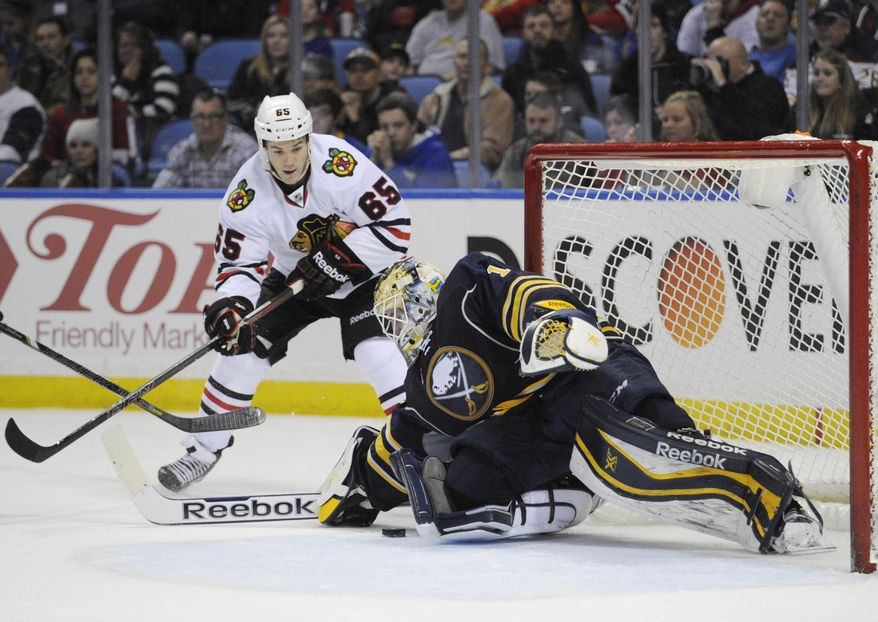 Chicago Black Hawks center Andrew Shaw (65) battles for a rebound as Buffalo Sabres goaltender Jhonas Enroth (1) makes  a save during the second period of an NHL hockey game in Buffalo, N.Y., Sunday, March 9,  2014. (AP Photo/Gary Wiepert)