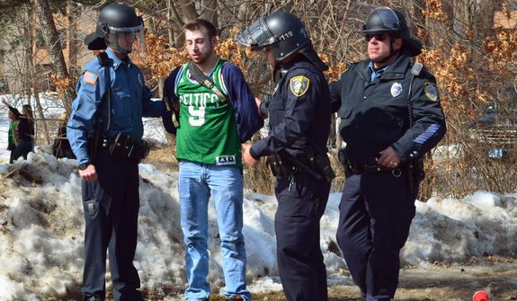 "Police detain a participant in the pre-St. Patrick's Day ""Blarney Blowout"" near the University of Massachusetts in Amherst, Mass. on Saturday, March 8, 2014.  Amherst police said early Sunday that 73 people had been arrested after authorities spent most of the day Saturday attempting to disperse several large gathering around the UMass campus for the party traditionally held the Saturday before spring break. The partying carried through Saturday evening into early Sunday, and Amherst Police Capt. Jennifer Gundersen said in a statement that police were busy with numerous reports of fights, noise and highly intoxicated individuals. (AP Photo/The Republican, Robert Rizzuto)  MANDATORY CREDIT"