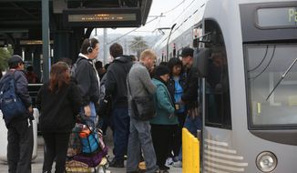 Pedestrians board a train at Union Station Friday March 7, 2014 in Los  Angeles. Americans are boarding public buses, trains and subways in greater numbers than any time since the suburbs began to boom. Nearly 10.7 billion trips in 2013, to be precise, the highest number since 1956.  (AP Photo/Nick Ut)