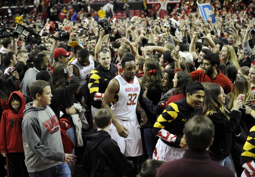 Maryland's Dez Wells (32) and others make their way through the mob after Maryland fans rushed the floor after beating Virginia 75-69 in overtime of an NCAA college basketball game, Sunday, March 9, 2014, in College Park, Md. (AP Photo/Nick Wass)
