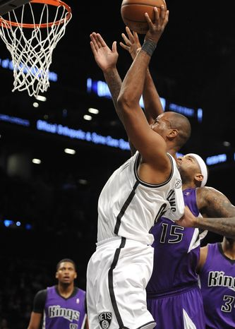 Brooklyn Nets' Jason Collins, foreground, takes aim for the basket over Sacramento Kings' DeMarcus Cousins (15) in the first half of an NBA basketball game on Sunday, March 9, 2014, at Barclays Center in New York. (AP Photo/Kathy Kmonicek)