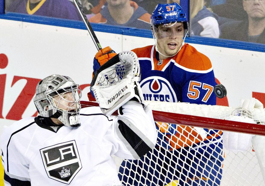 Los Angeles Kings goalie Jonathan Quick (32) makes the save as Edmonton Oilers David Perron (57) watches the puck hit the post during second period NHL hockey action in Edmonton, Alta., on Sunday March 9, 2014.  (AP Photo/The Canadian Press, Jason Franson)