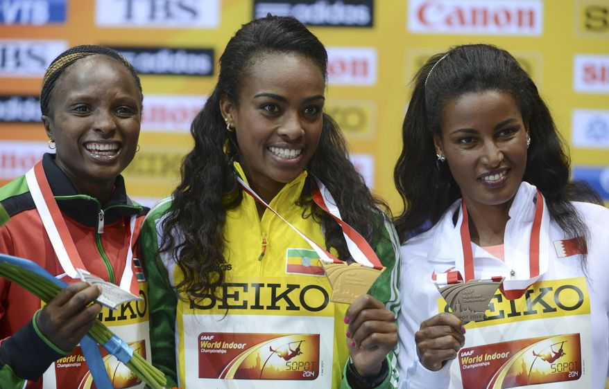 Ethiopia's gold medal winner Genzebe Dibaba is flanked by Kenya's silver medal winner Hellen Onsando Obiri, left, and Bahrain's bronze medal winner Maryam Yusuf Jamal during the ceremony for the women's 3000m at the Athletics Indoor World Championships in Sopot, Poland, Sunday, March 9, 2014.  (AP Photo/Alik Keplicz)