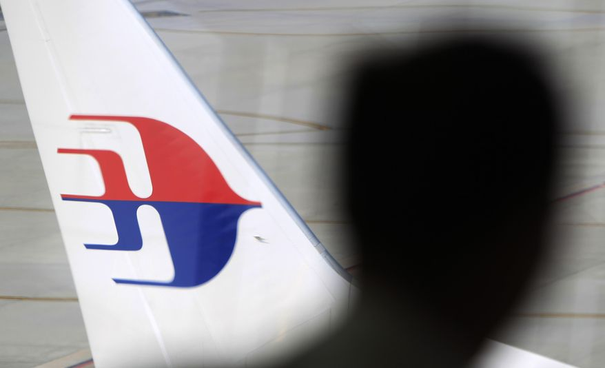 A man looks out from a viewing gallery as a Malaysia Airlines aircraft sits on the tarmac at Kuala Lumpur International Airport in Sepang, Malaysia, Sunday, March 9, 2014. Vietnamese ships and planes hunting for a missing Malaysian jetliner have found no wreckage close to where they spotted two large oil slicks.  The Boeing 777 carrying 239 people disappeared off radar screens early Saturday less than an hour after taking off from Kuala Lumpur bound for Beijing. (AP Photo/Lai Seng Sin)