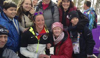 Tatyana Mcfadden of United States, second left in the first row, poses with her Russian birth mum, second right in the first row, after her race during the ladies 12km cross country ski, sitting event at the 2014 Winter Paralympic, Sunday, March 9, 2014, in Krasnaya Polyana, Russia. (AP Photo/Rob Harris)