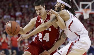 Wisconsin's Bronson Koenig (24) is guarded by Nebraska's Terran Petteway, right, in the first half of an NCAA college basketball game in Lincoln, Neb., Sunday, March 9, 2014. (AP Photo/Nati Harnik)