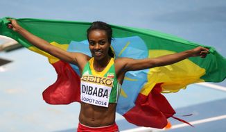 Ethiopia's Genzebe Dibaba carries the national flag after winning the women's 3000m final during the Athletics World Indoor Championships in Sopot, Poland, Sunday, March 9, 2014. (AP Photo/Petr David Josek)