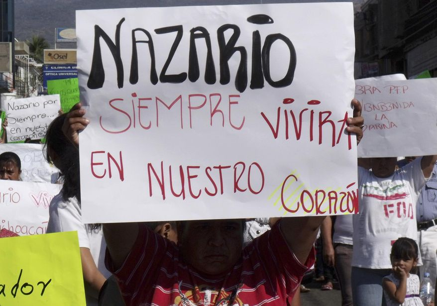 "FILE - In this Dec. 12, 2010 file photo, a man holds a sign that reads in Spanish ""Nazario will always live in our hearts,"" referring to La Familia drug cartel leader Nazario Moreno Gonzalez during a demonstration after the government announced he was killed in Apatzingan, Mexico. Years later on Sunday, March 9, 2014, officials say they are trying to determine if a man killed in an early morning shootout is Moreno. Some residents of Michoacan have reported seeing Moreno as his former cartel, La Familia Michoacana, was morphing into the more vicious and powerful Knights Templar. (AP Photo/Primera Plana, File)"