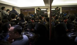 Journalists crowd outside a hotel holding room prepared for relatives or friends of passengers aboard a missing Malaysian Airlines jetliner, in Beijing, China Sunday, March 9, 2014. Planes and ships from across Asia resumed to the hunt Sunday for a Malaysian jetliner missing with 239 people on board for more than 24 hours, while Malaysian aviation authorities investigated how two passengers were apparently able to get on the aircraft using stolen passports. (AP Photo/Andy Wong)