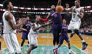 Boston Celtics' Rajon Rondo (9) passes in front of Detroit Pistons' Greg Monroe (10) in the first quarter of an NBA basketball game in Boston, Sunday, March 9, 2014. (AP Photo/Michael Dwyer)