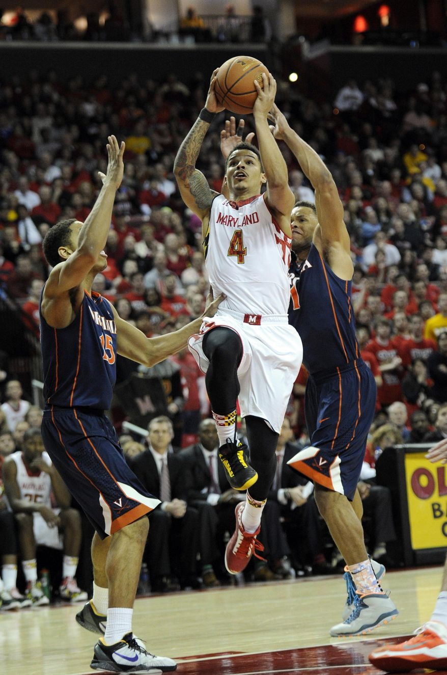 Maryland guard Seth Allen (4) goes to the basket against Virginia guard Malcolm Brogdon (15) and Justin Anderson during the second half of an NCAA college basketball game, Sunday, March 9, 2014, in College Park, Md. Maryland won 75-69 in overtime. (AP Photo/Nick Wass)