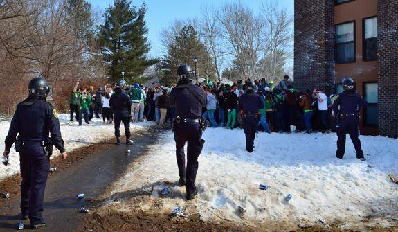 "Police surround participants in the pre-St. Patrick's Day ""Blarney Blowout"" near the University of Massachusetts in Amherst, Mass. on Saturday, March 8, 2014.  Amherst police said early Sunday that 73 people had been arrested after authorities spent most of the day Saturday attempting to disperse several large gathering around the UMass campus for the party traditionally held the Saturday before spring break. The partying carried through Saturday evening into early Sunday, and Amherst Police Capt. Jennifer Gundersen said in a statement that police were busy with numerous reports of fights, noise and highly intoxicated individuals. (AP Photo/The Republican, Robert Rizzuto)  MANDATORY CREDIT"