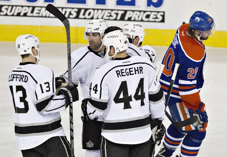 Los Angeles Kings Kyle Clifford (13), Jarret Stoll (28), Robyn Regehr (44) and Alec Martinez (27) celebrate a goal as Edmonton Oilers Luke Gazdic (20) skates past during second period NHL hockey action in Edmonton, Alberta, on Sunday March 9, 2014.(AP Photo/The Canadian Press, Jason Franson)
