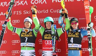 Germany's Felix Neureuther, center, celebrates on the podium after winning an alpine ski, men's World Cup slalom, flanked by second placed Germany's Fritz Dopfer, left, and third placed Henrik Kristoffersen, of Norway, in Kranjska Gora, Slovenia, Sunday, March 9, 2014. (AP Photo/Giovanni Auletta)