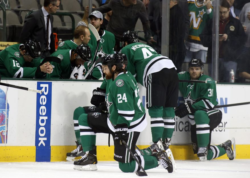 Dallas Stars right wing Alex Chiasson (12) bows his head on the bench as defenseman Jordie Benn (24) takes a knee on the ice after play was stopped in the first period of an NHL Hockey game against the Columbus Blue Jackets, Monday, March 10, 2014, in Dallas. Stars center Rich Peverly was taken to a hospital after a medical emergency. (AP Photo/Sharon Ellman)