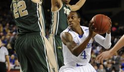 Delaware's Jarvis Threatt, right, drives to the basket as William and Mary's Tim Rusthoven, left, and Daniel Dixon block during the first half of the NCAA CAA Championship basketball game Monday, March 10, 2014, in Baltimore. (AP Photo/Gail Burton)