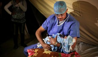 FILE - In this Monday, May 6, 2013 file photo, an obstetrician holds a baby after delivery at the Moroccan field hospital in Zaatari refugee camp near the Syrian border, in Mafraq, Jordan. An international charity organization Save Children has warned Monday, March 10, 2014 of a health care disaster in Syria with newborns dying in hospital incubators during power cuts and children having their limbs amputated for lack of alternative treatment. (AP Photo/Mohammad Hannon, File)