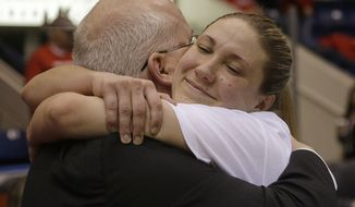 Marist guard Casey Dulin, right, hugs her head coach Brian Giorgis before the trophy presentation ceremony after winning an NCAA woman's MAAC conference championship basketball game against Quinnipiac in Springfield, Mass., Monday, March 10, 2014. Marist won 70-66. (AP Photo/Stephan Savoia)