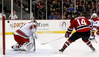 New Jersey Devils center Adam Henrique (14) scores a goal on Carolina Hurricanes goalie Anton Khudobin, of Kazakhstan, during the second period of an NHL hockey game, Saturday, March 8, 2014, in Newark, N.J. (AP Photo/Julio Cortez)