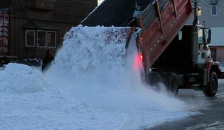 A Nome public works truck dumps a load of snow onto Front Street on Sunday, March 9, 2014, in Nome, Alaska. The snow was trucked in to provide a trail for mushers to the finish line of the Iditarod Trail Sled Dog Race. (AP Photo/Mark Thiessen)