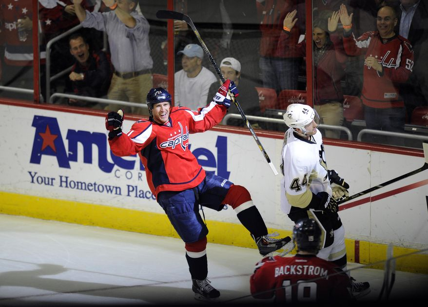 Washington Capitals center Brooks Laich (21) celebrates a goal  scored by teammate  Nicklas Backstrom (19) of Sweden. as Pittsburgh Penguins defenseman Brooks Orpik (44) skates past during the second period of an NHL hockey game, Monday, March 10, 2014, in Washington. (AP Photo/Nick Wass)