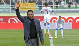 Former Brazilian soccer star Pele waves to the crowd before the kick off of the friendly soccer match Algeria vs Slovenia at Blida stadium, Algeria, Wednesday, March 5 , 2014. The match takes place ahead of the 2014 FIFA World Cup starting next June. (AP Photo/Sidali Djarboub)