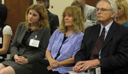 In this photo from June 22, 2012, Dr. Ann Kristin Neuhaus, center, sits between two of her attorneys, Kelly Kauffman, left, and Bob Eye, as the Kansas State Board of Healing Arts decides to revoke her medical license, in Topeka, Kan. A Kansas judge has overturned the state medical board's revocation of Neuhaus's license over her referrals of young patients for late-term abortions. (AP Photo/John Hanna)