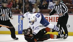 Toronto Maple Leafs' Tim Gleason, top, and Anaheim Ducks' Patrick Maroon fall to the ice as they fight during the first period of an NHL hockey game on Monday, March 10, 2014, in Anaheim, Calif. (AP Photo/Jae C. Hong)