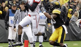 FILE -  In this Oct. 3, 2009, file photo, Arkansas State's Brandon Thompkins, left, catches a touchdown pass over Iowa's William Lowe during the second quarter of an NCAA college football game in Iowa City, Iowa.  Lowe, one of 13 Iowa football players hospitalized after a high-intensity workout in 2011, filed a lawsuit Monday, March 10, 2014, against the university claiming the university's negligence caused him physical and mental harm. (AP Photo/Charlie Neibergall, File)