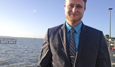 In this photo taken on Thursday, March 6,2 014, Lucas Overby, a 27-year-old Pinellas County resident, campaigns for Congress in Dunedin, Fla. Overby is the Libertarian candidate running against Democrat Alex Sink and Republican David Jolly. (AP Photo/Tamara Lush)