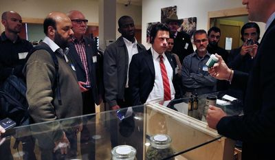 ** FILE ** In this Oct. 23, 2013, Norton Arbelaez, right, the owner of River Rock marijuana dispensary, shows his products to foreign lawmakers, Julio Bango, of Uruguay, second from left, Larry Campbell, of Canada, third from left, and Fernando Belaunzaran, of Mexico, fifth from left, during a tour of his business in Denver. (AP Photo/Brennan Linsley, File)
