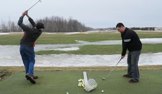 Brandon Cerecke, left, and Ben Johnson, two of the new owners of Sunset Coast Golf Center in St. Joseph, Mich., take advantage of a break in the weather to practice on their driving range, Tuesday, March 11, 2014. A winter storm warning has been issued for Wednesday for much of Southwest Michigan as a winter storm is expected to move through the area. (AP Photo/The Herald-Palladium, Don Campbell)