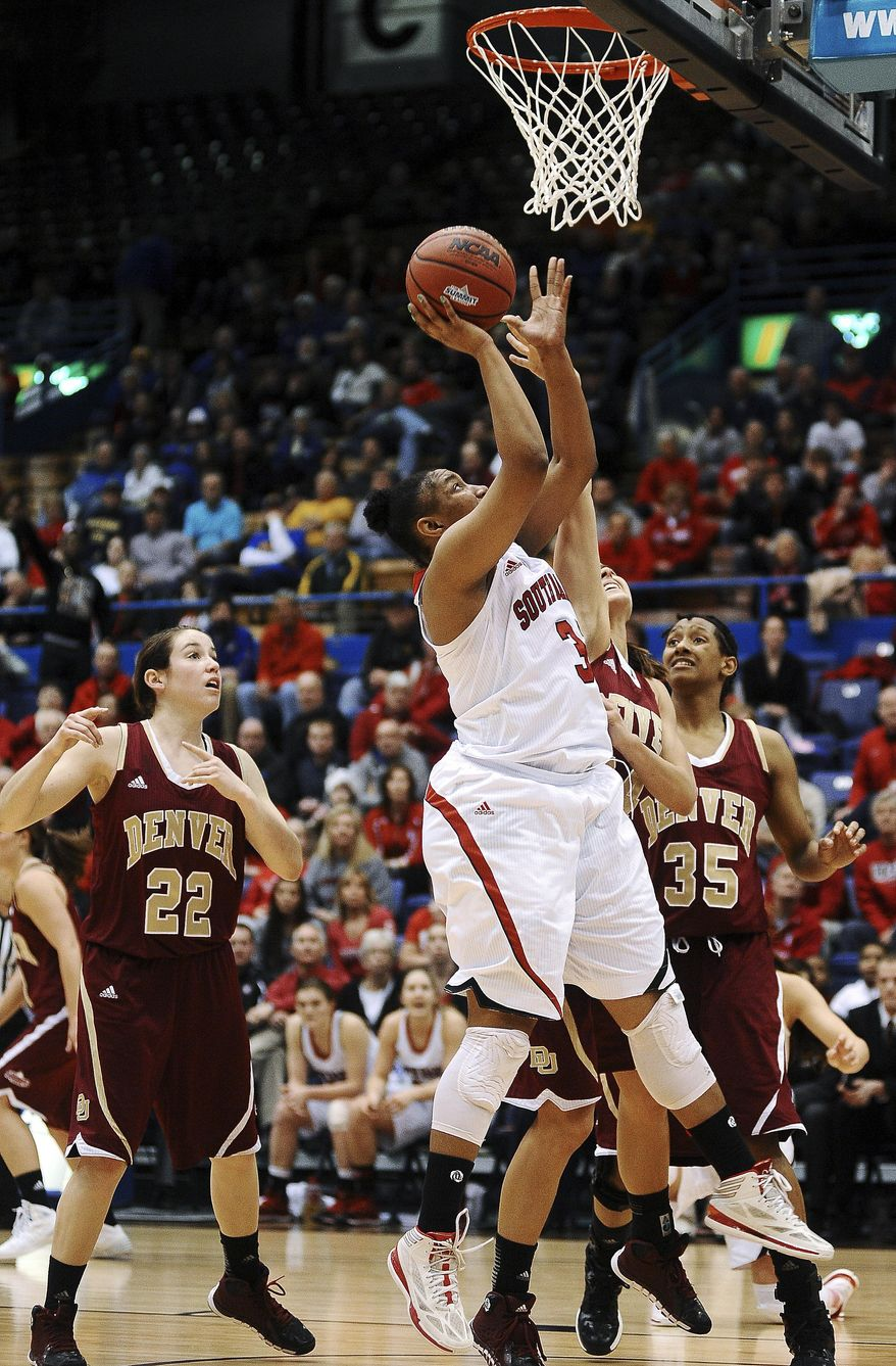 South Dakota's Polly Harrington (33) goes up for a shot over Denver defenders during the second half of an NCAA college basketball game for the championship of the Summit League women's tournament Tuesday, March 11, 2014, in Sioux Falls, S.D. South Dakota won 82-71. (AP Photo/Argus Leader, Joe Ahlquist) NO SALES