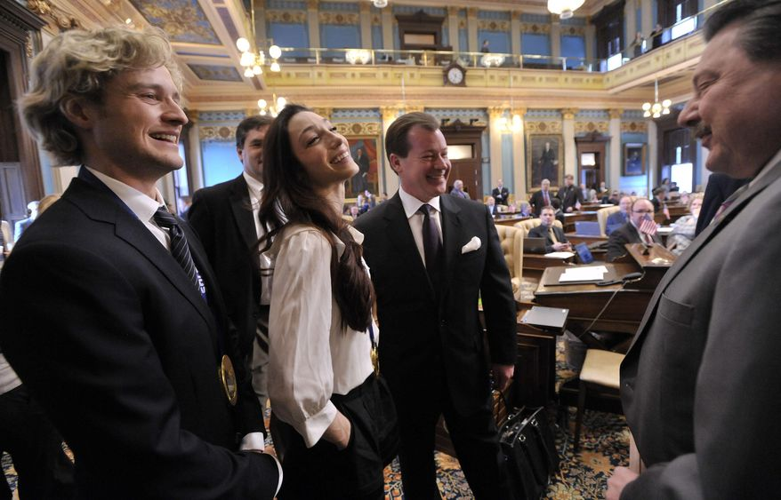 Senate Majority Leader Randy Richardville, center, introduces Sen. Mike Kowal, R-White Lake, right, to Michigan's olympic gold medal figure skaters, Charlie White, left, and Meryl Davis on the floor of the Senate at the Capitol Tuesday morning, March 11, 2014, in Lansing, Mich. Michigan Gov. Rick Snyder and lawmakers paid tribute to the pair.  (AP Photo/Detroit News, Dale G. Young)  DETROIT FREE PRESS OUT, MAGS OUT, MANDATORY CREDIT