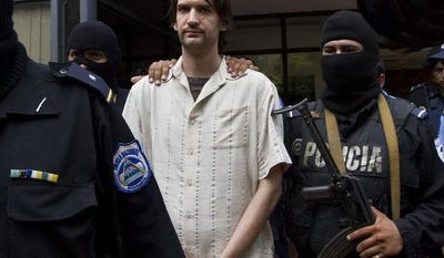 "FILE - This April 22, 2013 file photo shows Nicaragua's National Police agents escorting US citizen Eric Justin Toth to be presented to the press at a police station in Managua, Nicaragua. A former Washington private school teacher who was captured in Nicaragua after a year on the FBI's ""Ten Most Wanted"" fugitives list is scheduled to be sentenced in a child pornography case. Eric Toth's hearing is set for Tuesday in Washington. (AP Photo/Esteban Felix, File)"