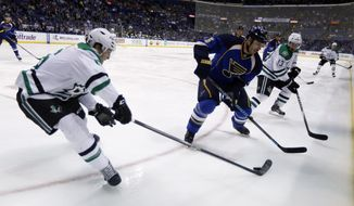Dallas Stars' Ryan Garbutt, left, and St. Louis Blues' Barret Jackman, center, chase after a loose puck as Stars' Ray Whitney (13) watches during the first period of an NHL hockey game Tuesday, March 11, 2014, in St. Louis. (AP Photo/Jeff Roberson)
