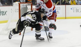 Pittsburgh Penguins' Sidney Crosby (87) and Washington Capitals' Dmitry Orlov (81), of Russia, chase the puck during the second period of an NHL hockey game, Tuesday, March 11, 2014, in Pittsburgh. (AP Photo/Keith Srakocic)