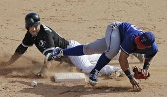 Chicago White Sox's Micah Johnson, left, steals second base as the throw eludes Texas Rangers second baseman Rougned Odor in the ninth inning of a spring exhibition baseball game Tuesday, March 11, 2014, in Glendale, Ariz. Johnson came around to score the winning run on a single by Alex Liddi to give the White Sox a 7-6 win. (AP Photo/Mark Duncan)