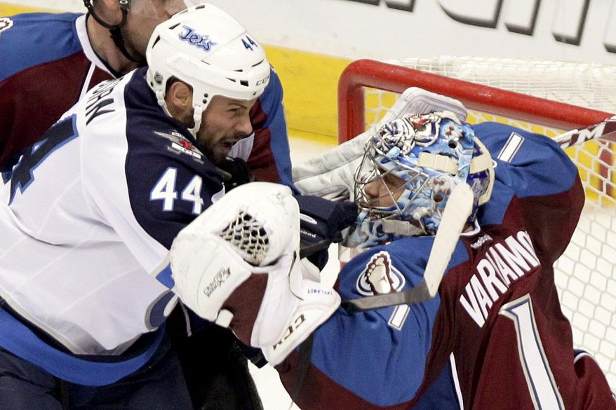 Winnipeg Jets'  Zach Bogosian (44) gets tangled up with Colorado Avalanche goalie Semyon Varlamov (1 ) during the first period of an NHL hockey game on Monday, March 10, 2014 in Denver. (AP Photo/Barry Gutierrez)