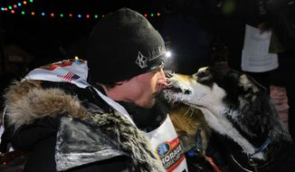 Dallas Seavey gets a kiss from one of his dogs after winning the 2014 Iditarod Trail Sled Dog Race in Nome, Alaska, Tuesday, March 11, 2014. (AP Photo/The Anchorage Daily News, Bob Hallinen)