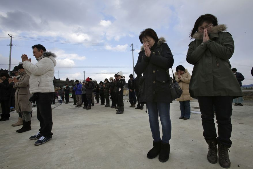 People observe a moment of silence in front of what is left of a disaster control center in an area devastated by the March 11, 2011 earthquake and tsunami, in Minamisanriku, Miyagi prefecture, Tuesday, March 11, 2014.  Japan is marking the third anniversary of the devastating earthquake and tsunami that left nearly 19,000 people dead or missing, turned coastal communities into wasteland and triggered a nuclear crisis.  (AP Photo/Shizuo Kambayashi)