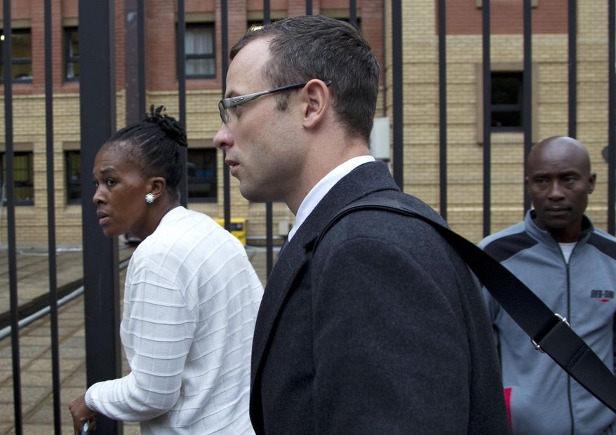 Oscar Pistorius, center, arrives at the high court for his murder trial in Pretoria, South Africa, Tuesday, March 11, 2014. Pistorius is charged with murder for the shooting death of his girlfriend, Reeva Steenkamp, on Valentines Day in 2013. (AP Photo/Themba Hadebe)