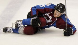 Colorado Avalanche's P.A. Parenteau (15) is knock out for the remainder of the regular season after a collision with Winnipeg Jets' Mark Stuart during the first period of an NHL hockey game on Monday, March 10, 2014 in Denver. (AP Photo/Barry Gutierrez)