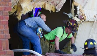 Fire fighters climb out of  huge hole caused by flat bed tractor and trailer that crashed into he side of the First Baptist Church in Center Star, Alabama, Monday March 10, 2014,  pinning the driver inside.(AP Photo/Times Daily, Matt McKean)