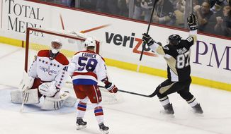 Pittsburgh Penguins' Sidney Crosby (87) celebrates scoring on Washington Capitals goalie Jaroslav Halak, of Slovakia, as Connor Carrick (58) skates by during the third period of an NHL hockey game, Tuesday, March 11, 2014, in Pittsburgh. The Penguins won 2-0. (AP Photo/Keith Srakocic)