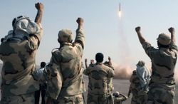 Members of the Iranian Revolutionary Guard watch a missile launch in July 2012. (Associated Press) **FILE**