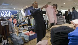 President Barack Obama,  with the help of store employee Susan Panariello, shops for sweaters at GAP clothing store in Manhattan during his unannounced visit, Tuesday, March 11, 2014. Obama used the visit to talk about raising the minimum hourly wage standards and applauded the GAP, who earlier in the year announced it was raising minimum wage for its employees. (AP Photo/Pablo Martinez Monsivais)