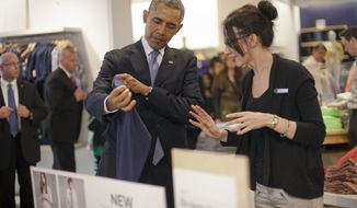 President Barack Obama, left, with the help of store employee Susan Panariello, right, shops at the GAP clothing store in Manhattan during his unannounced visit, Tuesday, March 11, 2014, in New York. Obama used the visit to talk about raising the minimum hourly wage standards and applauded the GAP, who earlier in the year announced it was raising minimum wage for its employees. (AP Photo/Pablo Martinez Monsivais)